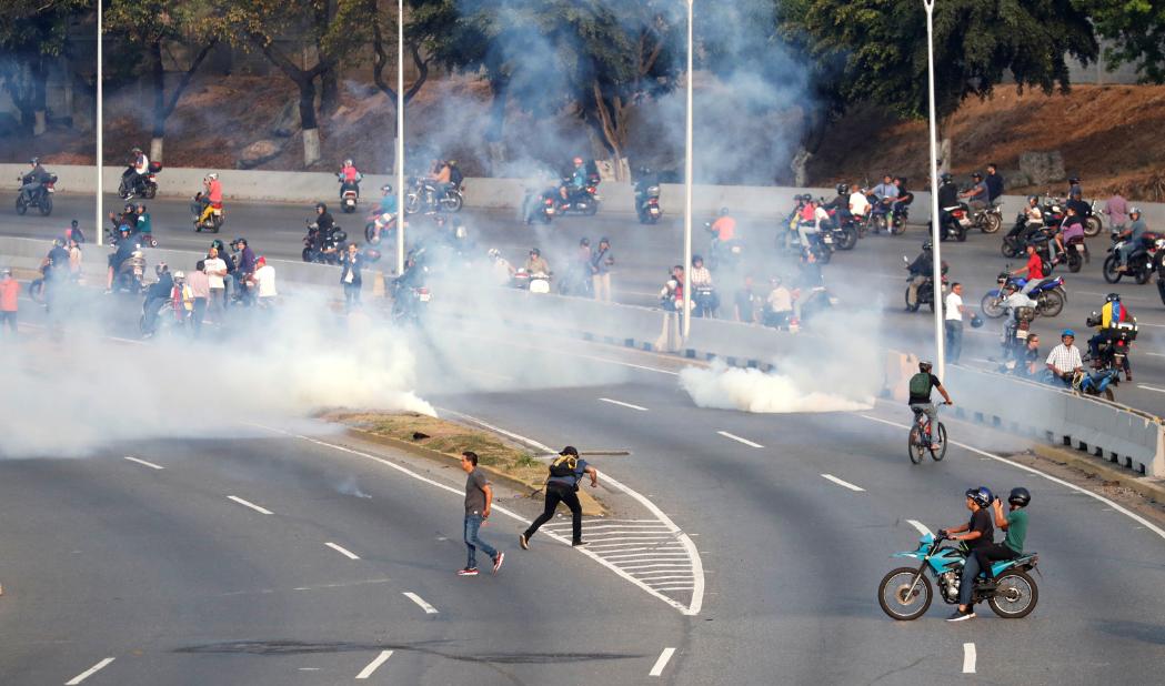 Gás lacrimogêneo é disparado contra Guaidó durante reunião com grupo de homens em uniformes militares