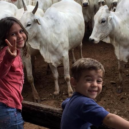 Heitor e Maria Eduarda olhando o gado no curral em Mineiros (GO). Envio de Beatriz Fusco